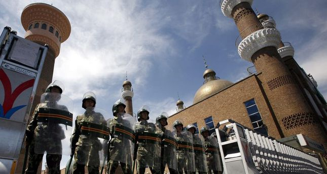 Chinese soldiers in riot gear stand guard across the entrance to a large mosque in the centre of the city of Urumqi